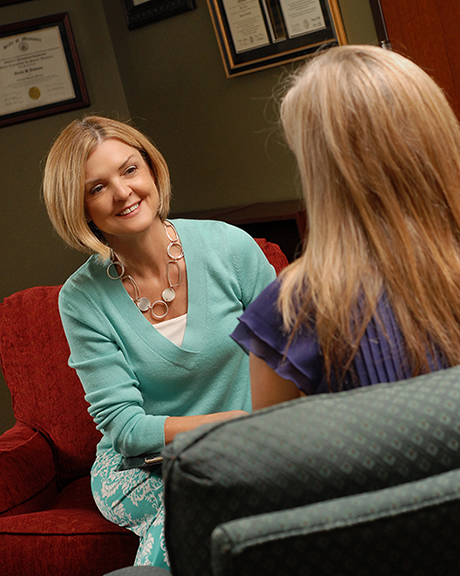 An image of Paula Johnson with Envision Counseling providing therapy services to a young woman with the back of her head in view.